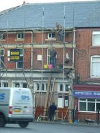 Workers on unsafe scaffolding outside a row of terraced shops in Oldham