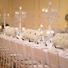 Una mesa elegante con flores blancas y candelabros