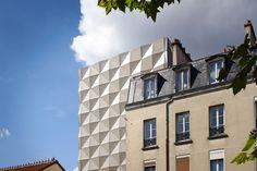 Folded tiles of perforated metal envelop this dance school in Paris