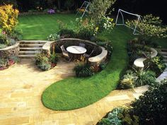 Pleasing Patio Designs: In this family garden, the kids can play on the spacious lawn while the adults hang out on the terrace. The two areas are divided by a snaking dry-stone and log wall, as well as by soft plantings. From DIYnetwork.com