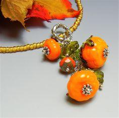 Semi-transparent orange lampwork glass pumpkin cluster pendant with SS findings.  SRA#O36