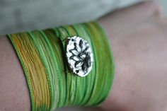 Beautiful Handpainted silk ribbon in sunset shades or yellow and gold through grass, handsitiched detailed edge and soft washed. This bracelet features a silvertone lotus charm, the charm reverses to the word enlightenment. The lotus represents the state of spiritual perfection and total mental purity. $30