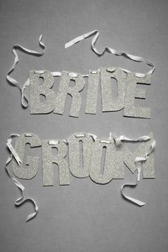love these silver glitter bride & groom banners, possibly for chairs.