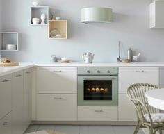 Grey-green extractor hood and oven in a white kitchen with white worktops and stainless steel handles.