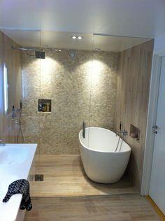 Flislagt bad med glassvegg- og dør inn til dusj og badekar. Steinmosaikk på en vegg. Like fliser på gulv og 2 vegger.