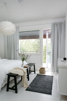 Casual white and grey Scandinavian bedroom with a bench and rug in darker tones to add a sense of dimension. .