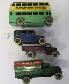 """Dinky No.25B Pre-war Covered Wagon """"Carter Paterson"""", green body, crack to rear end; pre war Motor Truck, dark red, white tyres, blue hubs, chipped paint; Dinky Toys pre war Taxi with driver, in blue and black, late version base, white tyres; Pre-war Double Deck Bus """"Dunlop Tyres"""", in green and cream with grey roof (4)  - Cheffins"""