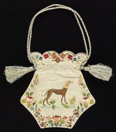 1820-1840 Ladies' bag of white moiré silk embroidered in colored silks. Shape is five-sided, flat, with a scalloped top. Borders of flower wreaths. Embroidered on one side with a greyhound and with a long-tailed bird on the other. Worked as two separate panels, joined. Lined in pale blue taffeta. Blue and white silk cord.