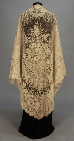 HANDMADE BUSSELS APPLIQUE LACE SHAWL, MID 19th C. Large cotton net triangle lavishly decorated with Point de Gaz and bobbin lace in a pattern of wisteria, hydrangea, lilac and other blossoms amid swags, ribbons and foliage.