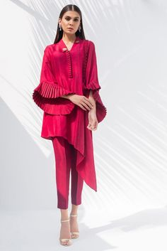 RAW SILK ASYMMETRICAL KURTA and pants Simple and refined, this red Raw Silk ensemble with ruffled sleeves and asymmetrical hemline is perfect for evening activities. * Plain Raw Silk pants All orders would take a minimum of 15 to 20 working days Pakistani Fashion Casual, Pakistani Dresses Casual, Pakistani Dress Design, Indian Fashion, Kurti Sleeves Design, Sleeves Designs For Dresses, Sleeve Designs, Indian Designer Outfits, Designer Dresses