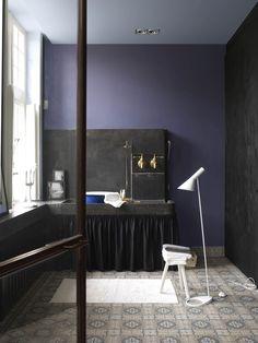 Flexa: Een badkamer om heerlijk te ontspannen. Met het warme van 'Blauwe bes' op de muur en een samenspel van friswitte accenten baad je in een oase van rust. De intense kleur 'Brownie' op de deurpost neemt je mee naar de 17e eeuw. Door het zachte 'Fluweelblauw' op het plafond waan je je in een schilderij van Vermeer.
