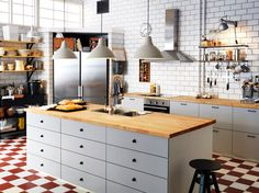 large white ikea family kitchen with island wooden worktops and stainless steel appliances