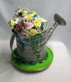 Watering Can - The flowers are gumpaste, as are the details on the can-with a dowel to support the spout. Airbrushed in silver and bronze and brown, and then added some brown petal dust to add to that rusty type of feeling.
