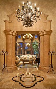 Mediterranean Entryway with High ceiling, Carpet, limestone tile floors, Chandelier