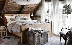 Makuuhuone, jossa puinen sänky, jossa valkoisia ja ruskeita tyynyjä ja peittoja.