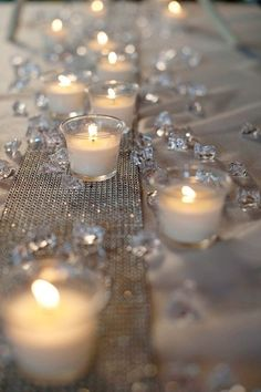 Get the same look at your wedding with Candle Impressions flameless tea lights, plastic faux crystals, and a silver table runner. This would be beautiful for a winter white themed wedding #candleimpressions #flamelesscandles