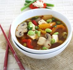 Fully Loaded Miso Soup {Protein Rich, Vegan} 2 large yellow onions 1 tsp chili-garlic sauce 3 garlic cloves, minced 2 cups sliced mushrooms of choice 5 cups low sodium vegetable stock 3 cups water 1 cup shelled edamame beans 1 large red bell pepper, coarsely chopped 1 large yellow bell pepper, coarsely chopped 1 package firm tofu, diced 6 Tbsp miso paste, or to taste 1 bundle green onion (scallions), finely chopped