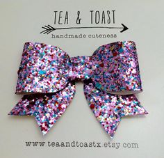 This Gorgeous, stunning, Glitter hair clip is made with only premium materials. It has a mix of light pink, aqua, gold & bits of red. The bow is