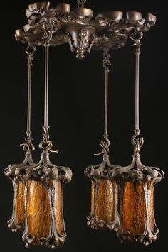 "AN ART NOUVEAU BRONZE AND AMBER GLASS CHANDELIER, POSSIBLY AUSTRIAN, CIRCA 1900. The stylized four leaf cornered ceiling mount suspending four pendant shades with textured amber glass cylinders held with stylized floral bronze mounts, in a natural bronze with parcel gilt. Length 28"", width 21""."