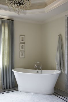 White stand alone bath tub placed in corner of bathroom | Amy Meier Design