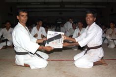 karate sankar is  giving the black belt and certificate his student Lakshmanan
