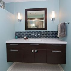 Dark floating cabinet with a white countertop and an under-mount sink by woodways http://woodwayscustom.com/gallery/bathrooms/contemporary-design-bathrooms/