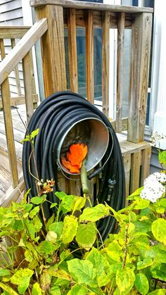 Hose holder that also holds my garden gloves and some tools from a big old pot.