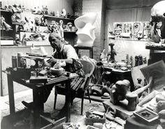 HENRY MOORE.This is a splendid portrait of the artist who is working on a maquette for a sculpture. All around him are maquettes and sculpture and on a shelf on a wall to his right is the celebrated Elephant Skull given to him by his Hampstead friends Sir Julian and Lady Juliette Huxley in 1966. Moore was fascinated by the skull and developed a number of graphic works exploring the internal and external spaces he found in this monumental object. These works were published as an album of etchi...