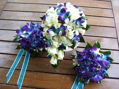 """Fully wired teardrop shape bridal bouquet of white roses, white and """"dyed"""" blue singapore orchids. Bridesmaid's bouquets of purple lissianthius, white and blue singapore orchids"""