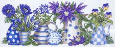 Pretty garden flowers - anemones, muscari, columbine and violas in blue and white spotted and striped jugs.