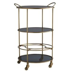 Serve your guests in style at your next soirée with this savvy bar cart. A minimalistic, antique brass-finished iron frame features three-tiered, black glass shelves to stylishly stow mixers and hors d'oeuvres.The top tray is removable and the circular bo Modern Baseboards, Glass Shelves In Bathroom, Art Deco Door, Vintage Bar Carts, Glass Bar, Wine Glass, Inviting Home, Beaded Chandelier, Modern Chandelier