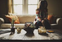 My living room. Repurposed wood table, Turning Triangles Terrarium (Urban), Anthropologie candle, cactus, orange and neutral. Photo by Ariel Renae