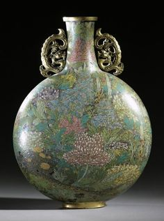 Pilgrim Flask  China, probably Beijing  Qianlong period  1736-95  Gilt-copper, cloisonné enamel   The flattened round form of this pilgrim flask  resembles the full moon, inspiring the alternative appellation 'moon flask'.  The handles are cast as coiled hornless dragons, called chilong. Blowsy peony blooms (mudan), set against a background of ornamental rocks and waterfalls, provide the decoration. The peony, a symbol of wealth, honour and nobility