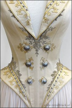"By Royal Black -- ""The Admiral"" is a uniform inspired corset top with high collar, lapels, spiky epaulets and semi-transparent detachable skirt pieces. / The corset is made from satin and is elaborately decorated with lace applique, synthetic leather cut work, silver beads, Swarovski crystals and metal buttons. The epaulets are made from sturdy thermoplast and are also decorated with beads, Swarovski crystals and buttons."