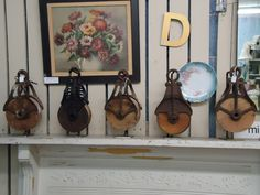 Love this idea, old pulleys are so cool.  Great vintage barn pulleys, now need the display hooks