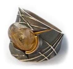 Ring | Elisenda De Haro. Rutilated quartz, silver and gold.....Connie Fox: Curved lines create visual movement on the band.