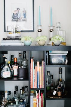 "Sneak Peek: A Crowded Seattle Home. ""While I love books (they are literally everywhere in our house) I'm happy to devote a few shelves to create a little bar. We love to create fun cocktails especially on our weekly at home date nights. The bookcase turned bar is from IKEA."" #sneakpeek"