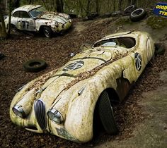 Ruined Jaguar racing car with Porshe in background