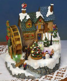 """Keramik Lichthaus Wasser-Mühle mit Musik und Beleuchtung - Herrlich viele Details gibt es bei dem Lichthaus """"Wassermühle"""" zu entdecken. Kein Wunder, dass der Weihnachtsmann viele gute Gaben durch den Kamin bringen möchte. Besonders schön: Das Mühlrad am Lichthäuschen und der Christbaum drehen sich und sind eindrucksvoll beleuchtet. Die Keramik liegt auf einem kleinen Berg und sieht einfach toll aus in Ihrer Porzellanhauslandschaft."""