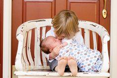 Irmão beijando recém-nascido. Fotos de Bebês recém-nascidos