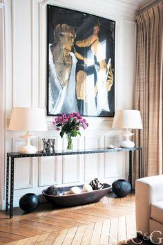 photographer apt in paris Stephane Kossmann living room console table herringbone wood floor white paneling large avant garde painting