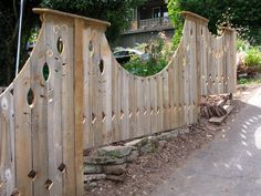 undulating lines of a recycled cedar art fence tackle a steep slope with the addition of stone and brick bottom (pig wire would also look interesting) -- janesbackyard.com