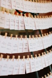 Great idea! Instead of designating a table to take up even more space at the reception, hang the place cards from a wire using cute little clothespins!