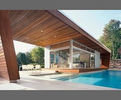 """The owners' first direction to us was to 'create something that's transparent, because we want to see through it,' "" architect Gisue Hariri says of a contemporary, ipe-paneled poolhouse in Wilton, Connecticut, her firm designed for a couple and their two children, ages 12 and 14. ""The pool and structure become one."" Outdoor furniture, Janus et Cie."