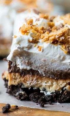 Butterfinger Chocolate Lush  has an oreo cookie crumb crust, a creamy peanut butter layer with crushed Butterfingers, a chocolate pudding layer, and a Cool Whip topping.