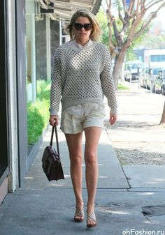 Эли Лартер в светлом, вязанном свитере и белых шортах