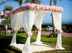Sheer elegance with this lovely #ChuppahCanopy decorated with florals. #BeachBride #OutdoorWedding