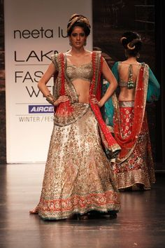 Gold traditionally embroidered, kundan work lehenga with a gold blouse and red dupatta.
