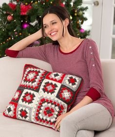 A fun arrangement of sizes and colours make crocheted granny squares pop in this pillow!