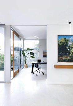 """""""We wanted a house that wasn't too precious, with a great flow, inside and out,"""" says Richard. """"We love the fact that this is a very forgiving home. It's fantastic in summer – the kids are always splashing away in the pool or racing around the garden.""""**Courtyard and study nook** White pendant lights hang over the desk, while in the hallway, a trio of lights from Halo Lighting in Perth illuminate a painting by Richard's late mother, Christobel Bennett. Floral display (on console), [Natural Art F"""
